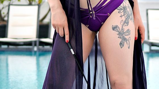 Rachael Richards in purple lingerie holding a riding crop in Chicago