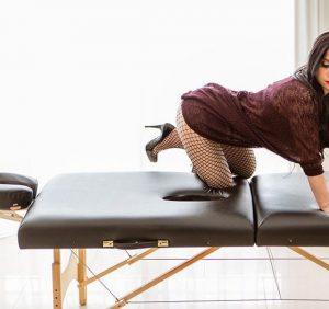Rachael Richards in black fishnet stockings kneeling on her table before giving an erotic massage