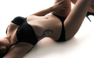 Rachael Richards lying down in black bra and panties before giving an Philadelphia erotic massage