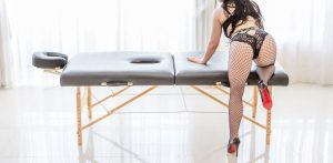 Rachael Richards in black fishnets kneeling again her table before giving an erotic massage