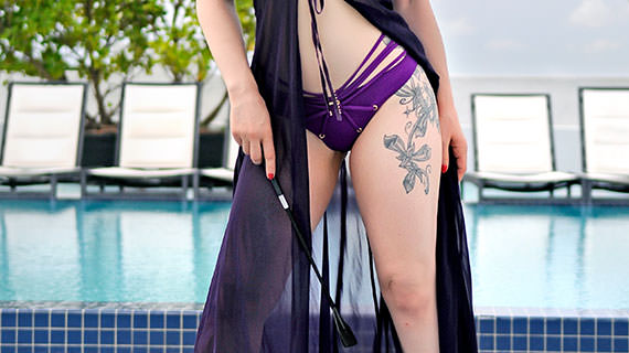 Rachael Richards in purple bikini with a riding crop about to give a Chicago erotic massage
