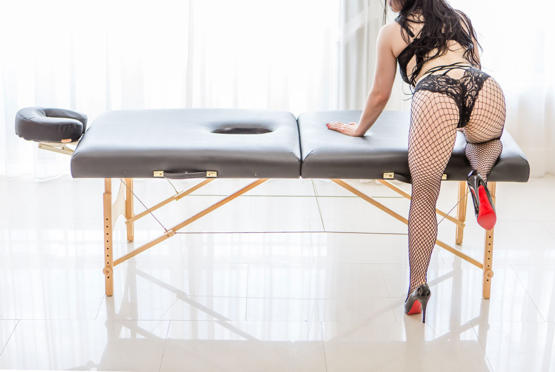 Rachael Richards in black fishnets kneeling again her table before giving an erotic massage in Chicago