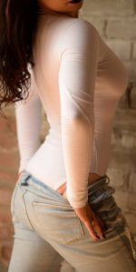 NYC erotic massage artist Rachael Richards in tight white bodysuit and jeans