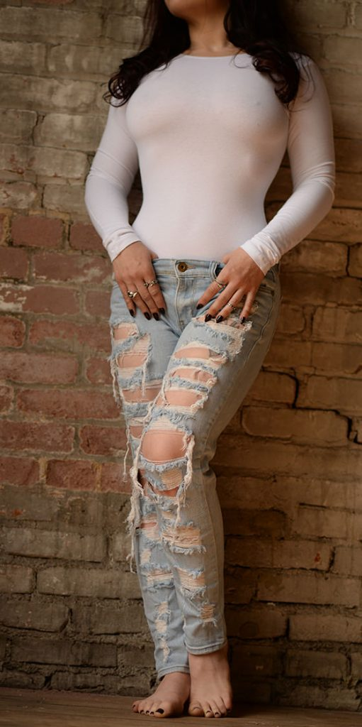 Erotic massage artist Rachael Richards in a white shirt and ripped jeans in New York City