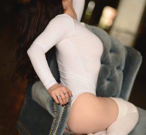 Rachael Richards posing in whitestockings before giving a sensual massage